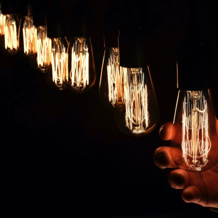 A row of filament style LED lightbulbs with a hand holding one of them
