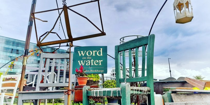 Blue chair, clear sky, sign saying Word on the water
