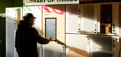 Man under sign that says 'library of things'