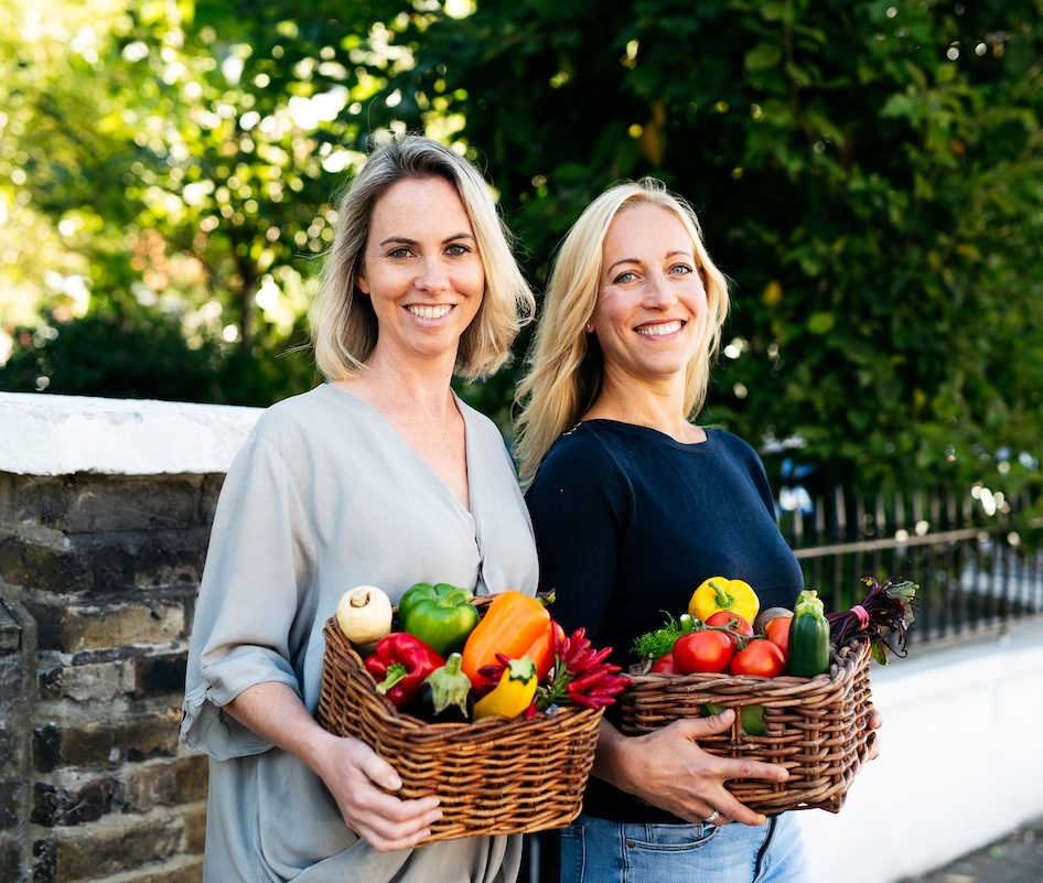 Two women with baskets of colourful vegetables